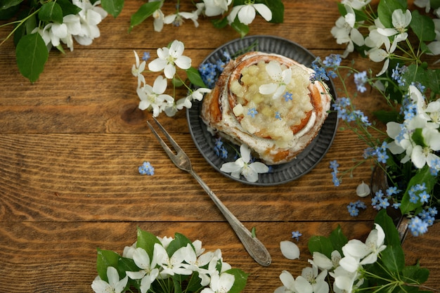 Kaneelbroodje en de lentebloemen op houten achtergrond