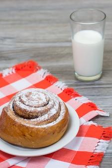 Kaneelbroodje op geruit tafelkleed en glas melk