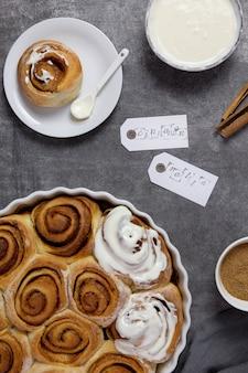 Kaneelbroodjes, broodjes in een ovenschaal met bruine suiker, gestremde roomsaus en kaneelstokjes op donkere achtergrond.