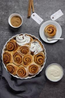 Kaneelbroodjes, broodjes in een ovenschaal met bruine suiker, wrongelroomsaus en kaneelstokjes op donker beton.