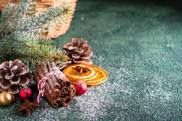 Kaneelstokjes, dennentakken en droge sinaasappelen op donkergroene achtergrond. christmas wenskaart