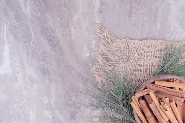 Kaneelstokjes in een houten beker met eiken takken rond.