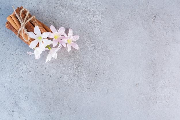 Kaneelstokjes in touw met witte en roze bloemen op grijze achtergrond.