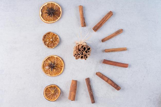 Kaneelstokjes met droge stukjes sinaasappel op de grond.