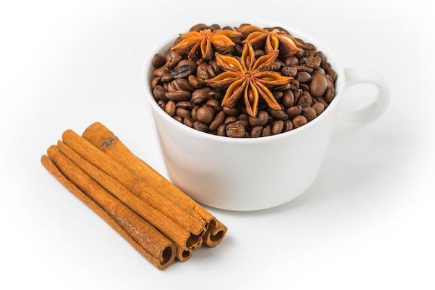 Kaneelstokjes naast een kop met koffiebonen