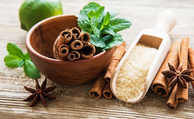 Kaneelstokjes, steranijs en bruine suiker op een houten tafel