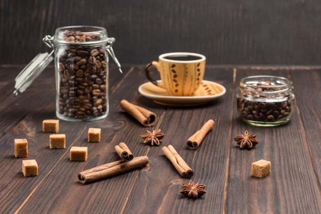 Kaneelstokjes, steranijs en stukjes bruine suiker. ð¡up koffie, koffiebonen in glazen potten.