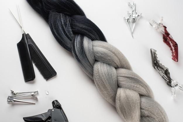 Kanekalon zwart en grijs haar op wit oppervlak met kammen en haaraccessoires