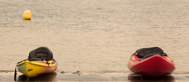 Kano's op het strand bij zonsondergang ruimte voor tekst