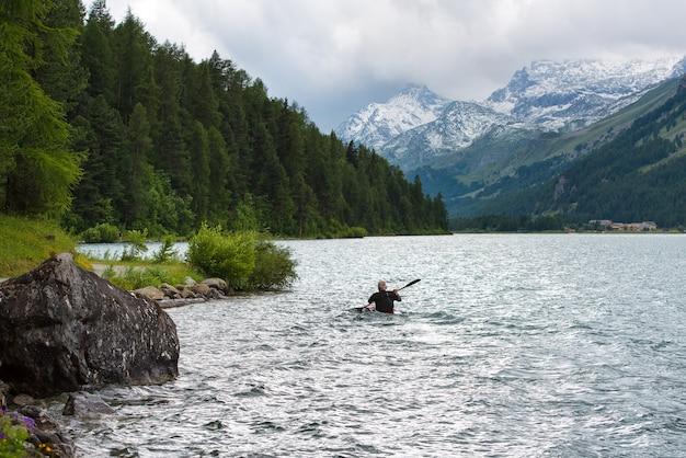 Kanovaarder in het meer van de alpen