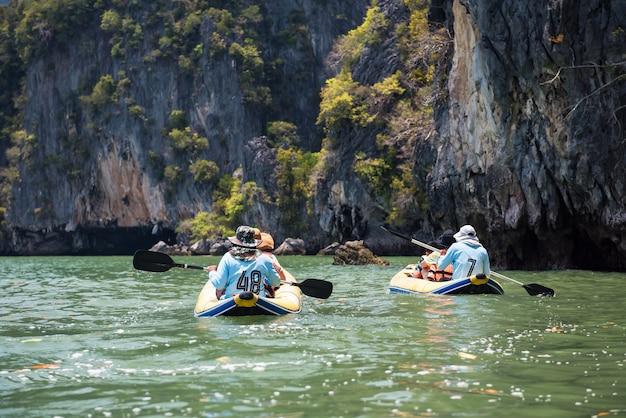 Kanovaren of kajakken voor toeristen naar karst-formaties in de baai van phang nga, thailand. beroemde reisactiviteit in de zomer van zuid-thais.
