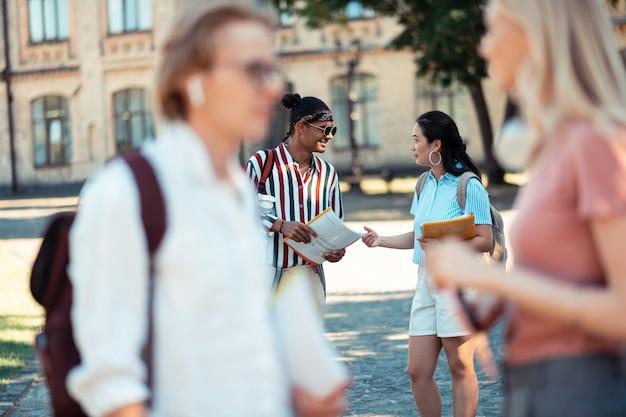 Kans om te praten. twee groepsgenoten die achter hun vrienden staan en hun huiswerk bespreken na de lessen op de campus.