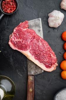 Kansas city rauwe biologische biefstuk gesneden, op zwarte tafel, bovenaanzicht