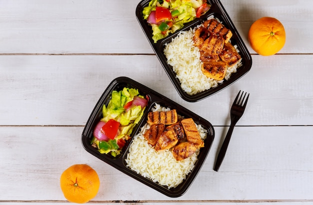 Kant-en-klaarmaaltijd om te eten op voedselcontainer met drank en sinaasappel.
