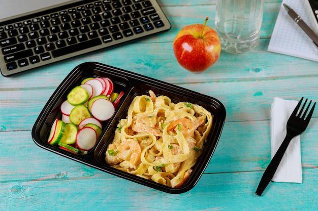 Kant-en-klaarmaaltijd om te eten op voedselcontainer met water en appel