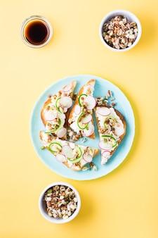 Kant-en-klare bruschetta met kwark, groenten en gekiemde granen op een bord op een gele tafel.