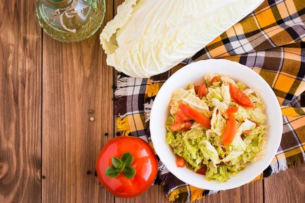 Kant-en-klare groentesalade, tomaten en chinese kool op een houten tafel, bovenaanzicht