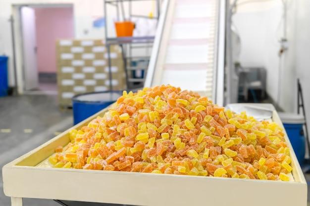 Kant-en-klare gumdrops ligt op een dienblad in een zoetwarenfabriek tegen de achtergrond van een wazig interieur van een werkplaats met een transportband