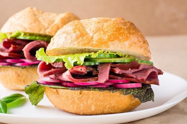 Kant-en-klare hamburger met pastrami, groenten en basilicum op een bord op ambachtelijk papier. amerikaans fastfood. detailopname