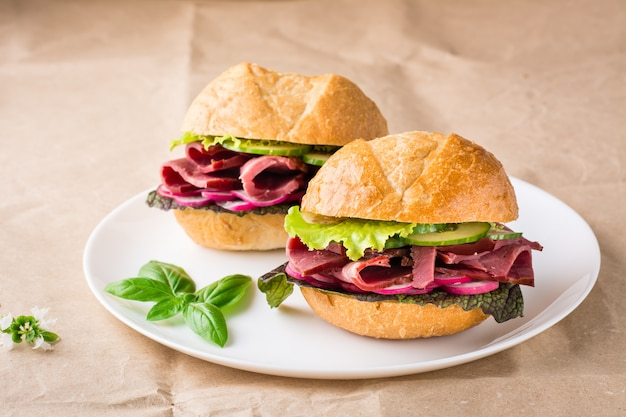 Kant-en-klare hamburgers met pastrami, groenten en basilicum op een bord op ambachtelijk papier. amerikaans fastfood.