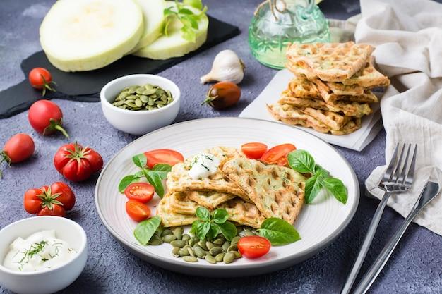 Kant-en-klare heerlijke courgettewafels, tomaten, basilicum en pompoenpitten op een bord op tafel. plantaardig dieetvoer