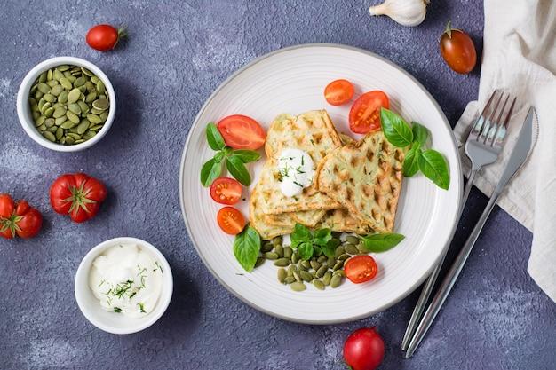 Kant-en-klare heerlijke courgettewafels, tomaten, basilicum en pompoenpitten op een bord op tafel. plantaardige dieetvoeding. bovenaanzicht