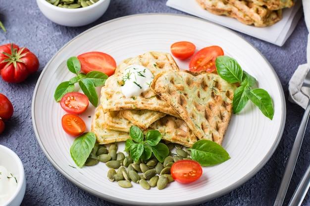 Kant-en-klare heerlijke courgettewafels, tomaten, basilicum en pompoenpitten op een bord op tafel. plantaardige dieetvoeding. detailopname