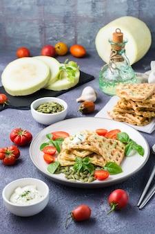 Kant-en-klare heerlijke courgettewafels, tomaten, basilicum en pompoenpitten op een bord op tafel. plantaardige dieetvoeding. verticale weergave
