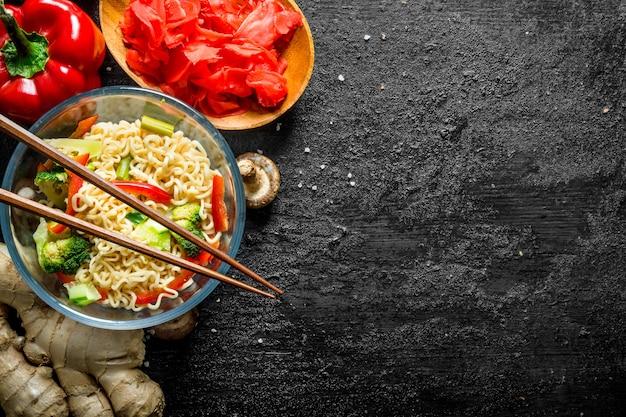Kant-en-klare instantnoedels met broccoli, peper en gember. op zwarte rustieke achtergrond