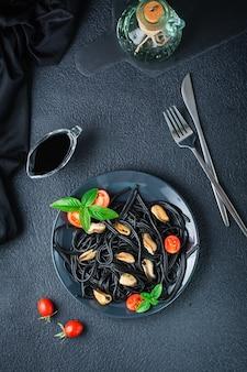 Kant-en-klare zwarte spaghetti met mosselen, tomaten en basilicum op een bord op een zwarte achtergrond. foodfotografie in donkere kleuren. boven- en verticaal aanzicht
