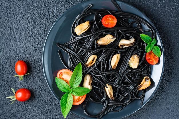 Kant-en-klare zwarte spaghetti met mosselen, tomaten en basilicum op een bord op een zwarte achtergrond. foodfotografie in donkere kleuren. bovenaanzicht. detailopname