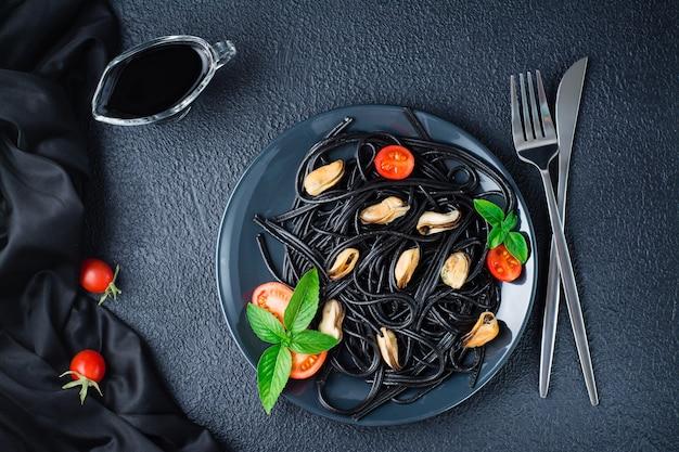 Kant-en-klare zwarte spaghetti met mosselen, tomaten en basilicum op een bord op een zwarte achtergrond. foodfotografie in donkere kleuren. bovenaanzicht