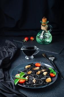 Kant-en-klare zwarte spaghetti met mosselen, tomaten en basilicum op een bord op een zwarte achtergrond. foodfotografie in donkere kleuren. verticale weergave