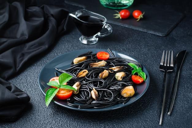 Kant-en-klare zwarte spaghetti met mosselen, tomaten en basilicum op een bord op een zwarte achtergrond. foodfotografie in donkere kleuren