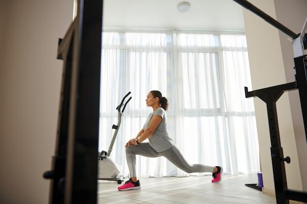 Kant full-length portret van jonge sportieve vrouw in grijze sportkleding lunges uitvoeren tegen grote ramen thuis