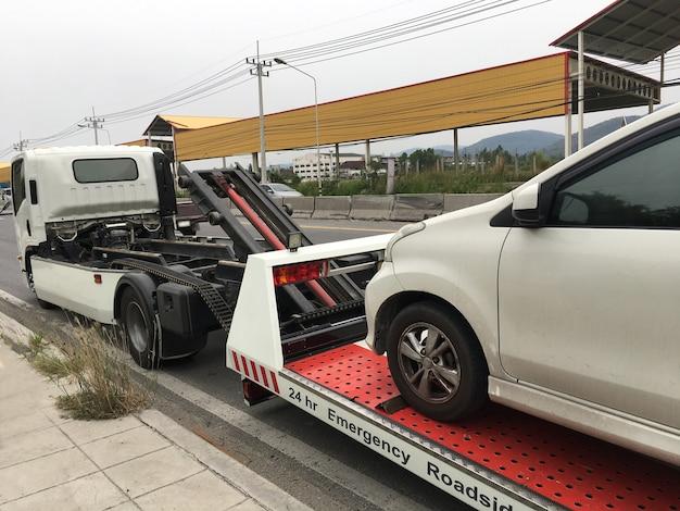 Kant van de weghulp gebroken auto op een slepenvrachtwagen op een kant van de weg