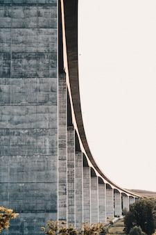 Kant van een hoge stenen snelweg brug met heldere witte lucht op de achtergrond