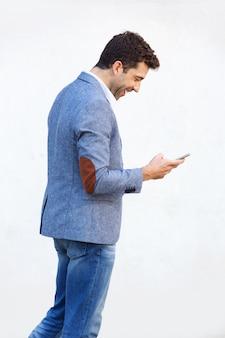 Kant van gelukkige jonge mens die mobiele telefoon op witte achtergrond met behulp van