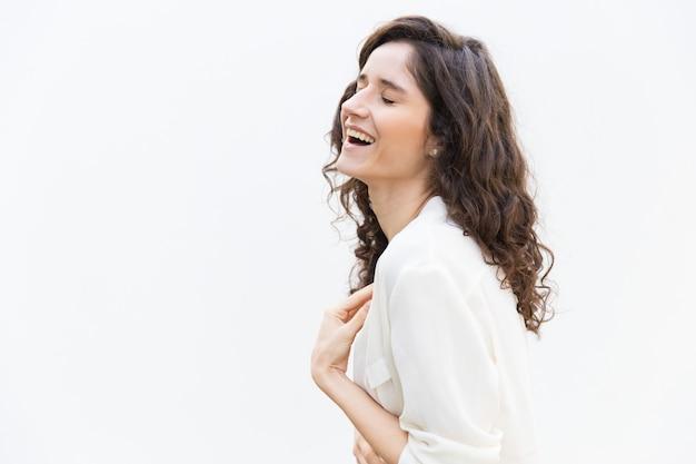 Kant van gelukkige vrolijke vrouw die met gesloten ogen lachen