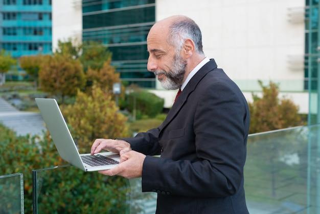 Kant van positieve volwassen bedrijfsleider die met laptop werkt