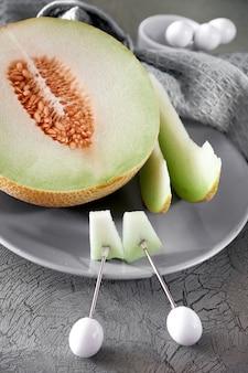 Kantaloepmeloen op grijze plaat wordt gesneden die