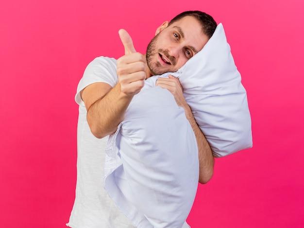 Kantelbare hoofd jonge zieke man knuffelde kussen en duim opdagen geïsoleerd op roze