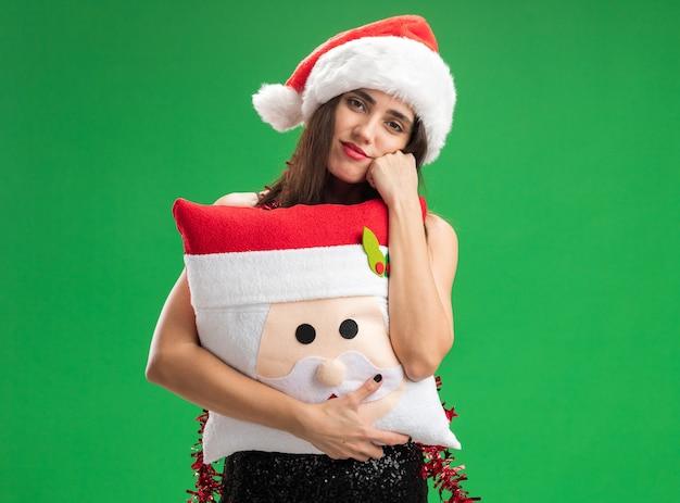 Kantelen hoofd jong mooi meisje met kerstmuts met slinger op nek met kerst kussen hand op wang geïsoleerd op groene muur te houden