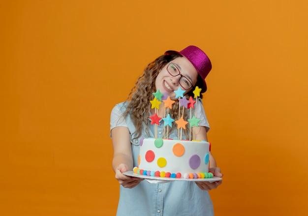 Kantelend hoofd glimlachend jong meisje dat glazen en roze hoed draagt die verjaardagstaart standhouden die op oranje muur wordt geïsoleerd