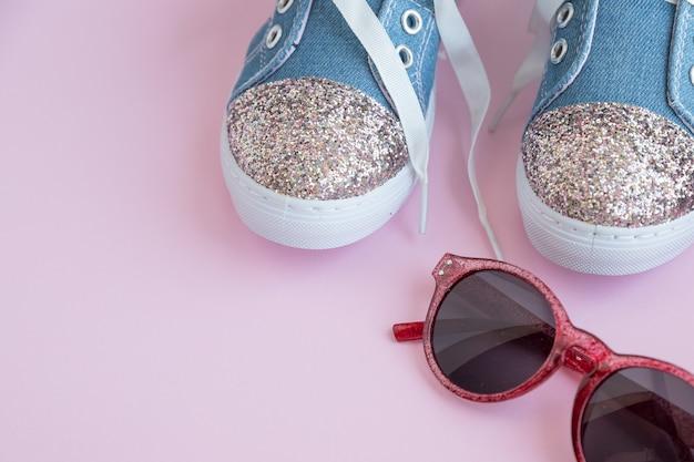Kanten sneakers van textiel voor kinderen. meisjes schoenen op roze muur. mode kinderschoeisel. slimme casual modieuze denim en glanzende schoenen. zonnebril en trendy kindersportschoenen. ruimte kopiëren. selectieve aandacht