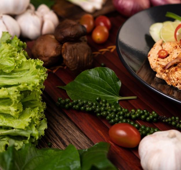 Kantonese sla, verse peperzaadjes, knoflook, tomaten, shiitake-paddenstoelen en rode uien op houten planken