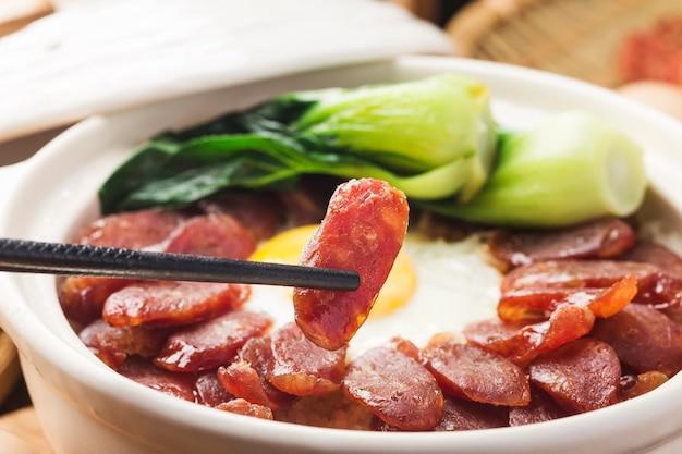 Kantonese stijl koken van claypotrijst met gewaxt vlees