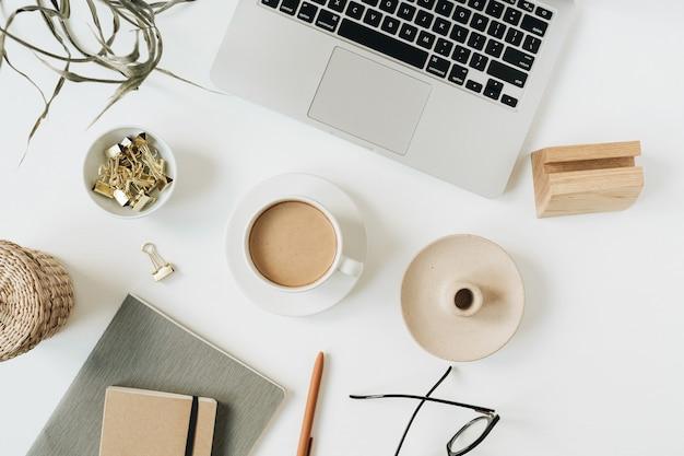 Kantoor aan huis bureau werkruimte met laptop, koffiekopje, notebook, bril, pen, groene planttak op wit oppervlak