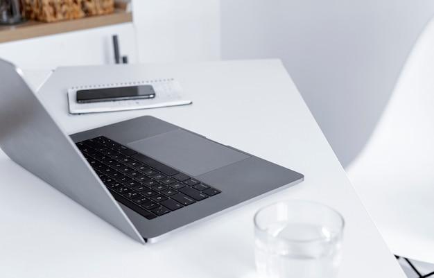 Kantoor aan huis met computer, notitieblok, glas water en smartphone. werken op afstand of online leren concept