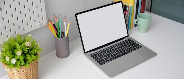 Kantoor aan huis met leeg scherm laptop, briefpapier, boeken en boom pot op witte tafel